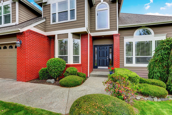 American beige house with red brick trim and dark blue front door. Concrete walkway with nicely trimmed bushes. Northwest, USA